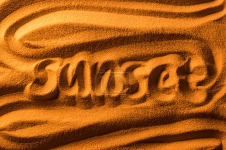 Photo for Top view of word sunset written in sand with smooth waves and color filter - Royalty Free Image