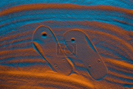 Photo pour Vue du dessus de la marque de tongs sur sable texturé avec filtre de couleur - image libre de droit