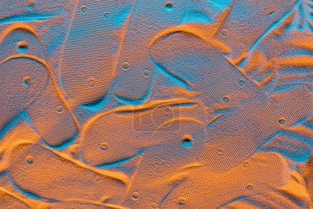 Photo pour Vue de dessus des marques de tongs texturées sur le sable avec le filtre de couleur - image libre de droit