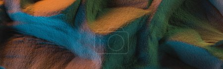 Photo pour Panoramic shot of textured sand with orange, green and blue lights - image libre de droit