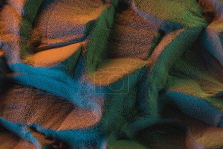 Foto de Vista superior de la arena texturizada con luces naranjas, verdes y azules - Imagen libre de derechos