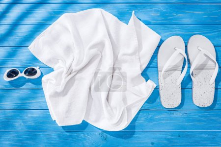 Photo for Top view of White crumpled towel, sunglasses and flip flops on blue wooden background - Royalty Free Image