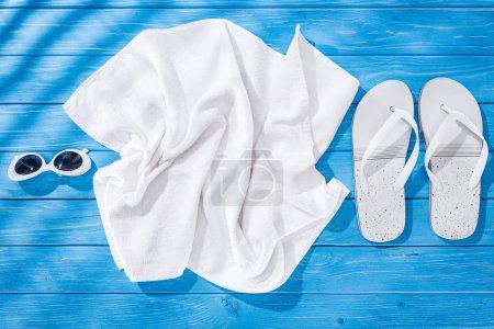 Photo pour Vue du dessus de la serviette froissée blanche, des lunettes de soleil et des tongs sur fond de bois bleu - image libre de droit