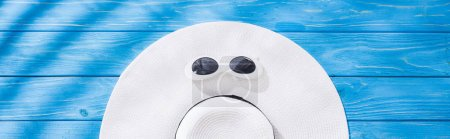 Photo for Panoramic shot of white floppy hat with black ribbon and sunglasses on blue wooden background - Royalty Free Image
