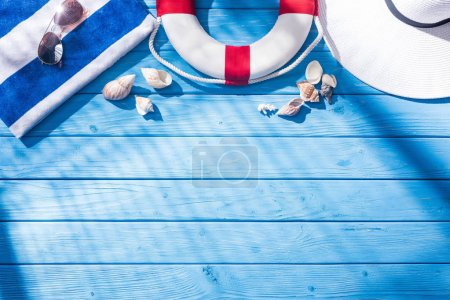 Photo for Top view of striped towel, sunglasses, lifebuoy, white floppy hat and seashells on blue wooden background with shadows and copy space - Royalty Free Image