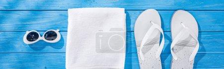 Foto de Foto panorámica de toalla plegado blanco, gafas de sol retro y chanclas sobre fondo de madera azul - Imagen libre de derechos