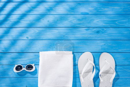 Photo for Top view of white folded towel, retro sunglasses and flip flops on blue wooden background with shadows and copy space - Royalty Free Image