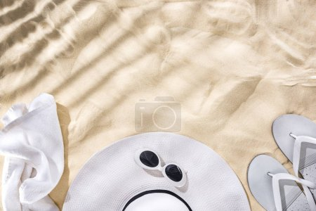 Photo pour Vue du haut de la serviette blanche, lunettes de soleil rétro, tongs et chapeau disquette avec ruban noir sur le sable avec des ombres et l'espace de copie - image libre de droit