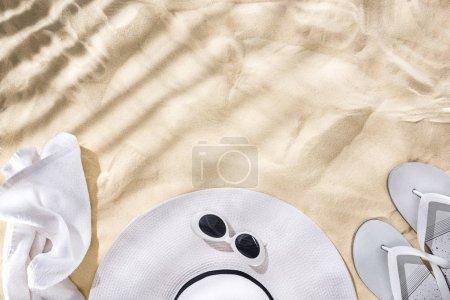 Foto de Top view of white towel, retro sunglasses, flip flops and floppy hat with black ribbon on sand with shadows and copy space - Imagen libre de derechos