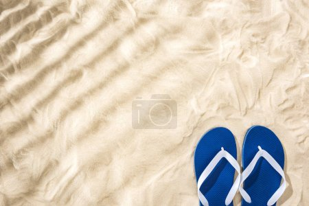 top view of white blue flip flops on sand with shadows and copy space