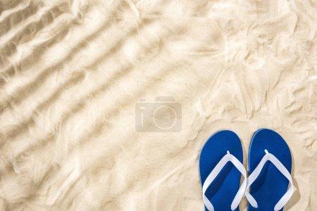 vue de dessus des tongs bleues blanches sur sable avec ombres et espace de copie