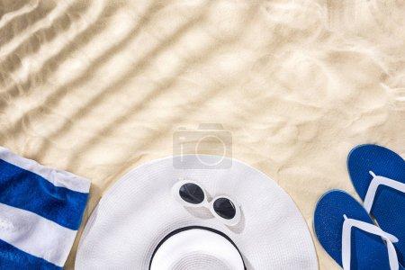 Foto de Top view of striped towel, retro sunglasses, floppy hat and blue flip flops on sand with shadows and copy space - Imagen libre de derechos