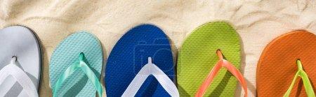Foto de Panoramic shot of white, turquoise, green and blue flip flops on sand - Imagen libre de derechos