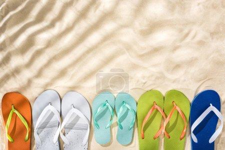 Foto de Vista superior de las chanclas blancas, turquesas, verdes y azules en la arena con sombras y copiar espacio - Imagen libre de derechos