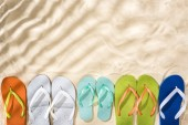 """Постер, картина, фотообои """"top view of white, turquoise, green and blue flip flops on sand with shadows and copy space"""""""
