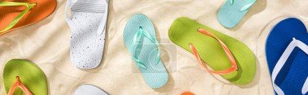 Photo pour Plan panoramique de tongs blanches, turquoises, vertes et bleues éparpillées sur le sable - image libre de droit