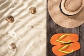 "Постер, картина, фотообои ""top view of orange flip flops and straw hat with black ribbon on wooden board and sand with seashells and copy space"""