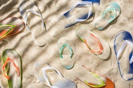 Foto de Vista superior de las chanclas turquesas, naranjas, azules y verdes dispersas en la arena con sombras - Imagen libre de derechos