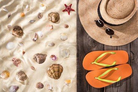 Photo pour Vue de dessus des coquillages et étoiles de mer sur sable avec tongs orange, chapeau de paille et lunettes de soleil sur panneau brun en bois - image libre de droit