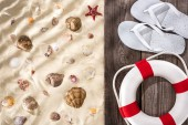 """Постер, картина, фотообои """"top view of flat lay with white flip flops and white rope lifebuoy on wooden brown board on ribbed sand background with seashells and starfish"""""""