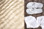 """Постер, картина, фотообои """"Top view of white flip flops and towel on wooden brown board and sand with copy space"""""""