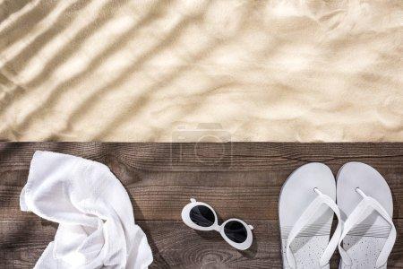 Photo pour Vue de dessus du sable avec espace de copie et serviette blanche, lunettes de soleil rétro et tongs sur panneau brun en bois - image libre de droit