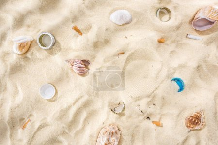 Photo for Top view of seashells, bottle caps, scattered cigarette butts, plastic bottle caps on sand - Royalty Free Image