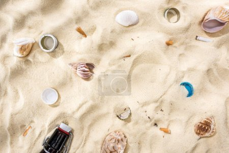 Photo for Top view of seashells, bottle caps, scattered cigarette butts and glass bottle on sand - Royalty Free Image