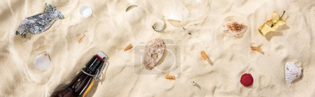 Photo pour Panoramic shot of seashells, bottle caps, scattered cigarette butts, apple core, glass bottle and candy wrapper on sand - image libre de droit