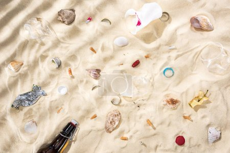 Photo pour Top view of seashells, scattered cigarette butts, apple core, plastic cups, glass bottle and candy wrapper on sand - image libre de droit