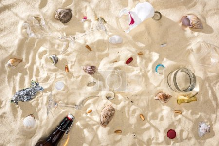 Photo pour Top view of seashells, glass bottle, scattered cigarette butts, broken glasses, apple core, plastic cups and candy wrapper on sand - image libre de droit
