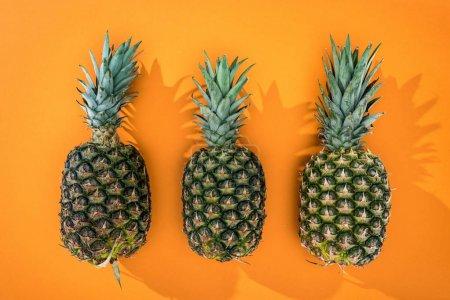 Photo pour Vue de dessus des ananas avec ombres latérales sur fond orange - image libre de droit