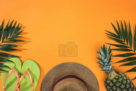 Photo pour Top view of pineapple, tropical leaves, green flip flops and brown straw hat on orange background with copy space - image libre de droit