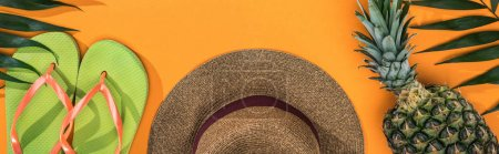 Photo pour Panoramic shot of pineapple, tropical leaves, green flip flops and brown straw hat on orange background - image libre de droit