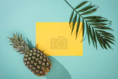 Photo pour Vue du dessus de l'ananas, feuille tropicale et carton jaune avec espace de copie sur fond turquoise - image libre de droit