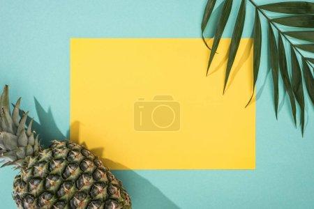 Foto de Vista superior de la piña, la hoja tropical y la tarjeta amarilla con espacio de copia sobre fondo turquesa - Imagen libre de derechos