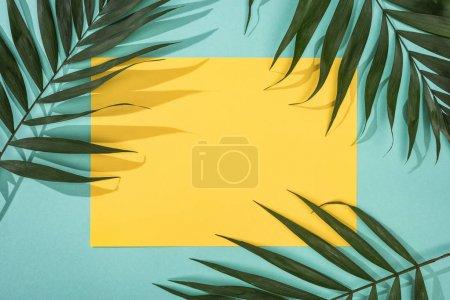 Widok z góry na tropikalne liście i żółtą kartkę z kopią miejsca na turkusowym tle