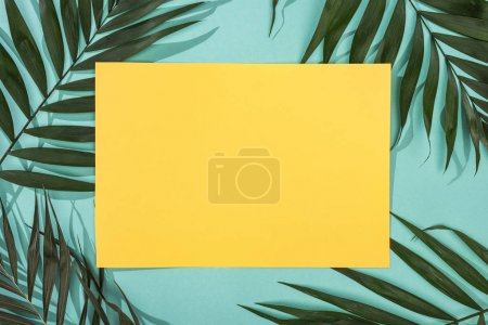 top view of tropical leaves and empty yellow card on turquoise background