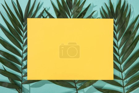 Photo for Top view of tropical leaves and empty yellow card on turquoise background - Royalty Free Image