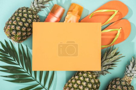 Photo for Top view of pineapples, tropical leaf, sunscreens, orange flip flops and empty card on turquoise background - Royalty Free Image