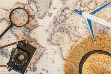 Vue du dessus de chapeau de paille, loupe, avion jouet et caméra de film sur la carte du monde
