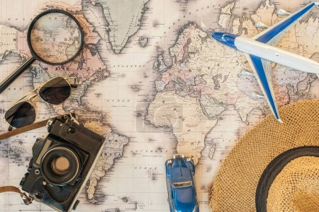 Top view of straw hat, magnifier, sunglasses, toy car, toy plane and film camera on world map