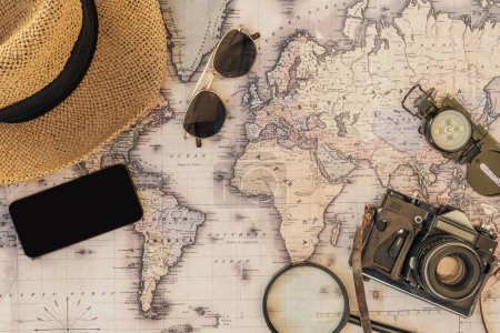 Draufsicht auf Strohhut, Sonnenbrille, Filmkamera, Lupe, Kompass und Smartphone mit leerem Bildschirm auf der Weltkarte