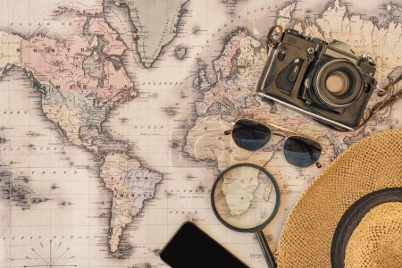Top view of straw hat, sunglasses, film camera, magnifier and smartphone with blank screen on world map