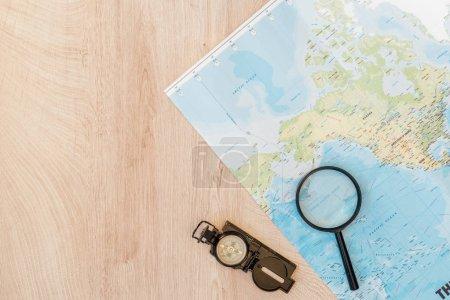 Weltkarte, Lupe und Kompass von oben auf Holzoberfläche