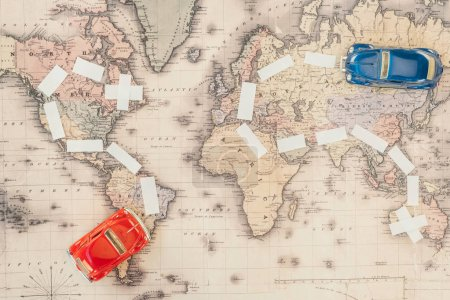 Photo for Top view of red and blue toy cars on world map - Royalty Free Image
