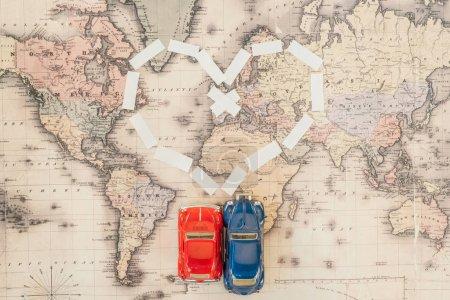 Photo pour Vue du dessus des voitures jouet rouge et bleu sur la carte du monde - image libre de droit