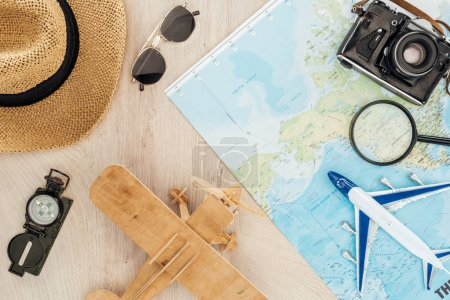 Top view of sunglasses, straw hat, compass, toy planes, magnifier, film camera and world map on wooden surface