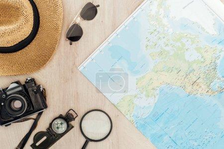 Sonnenbrille, Strohhut, Kompass, Lupe, Filmkamera und Weltkarte auf Holzoberfläche