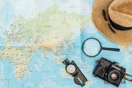 Top view of straw hat, compass, magnifier and film camera on world map